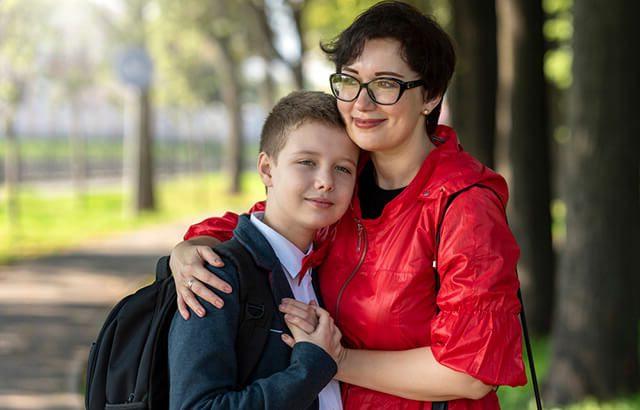 Mother hugging student child